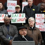 Father Rudolph Juarez of St. Patrick's Catholic Church discusses his support of the raised minimum wage outside St. Mary's Church on Wednesday, Nov. 25, 2015.