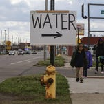 People walk along Saginaw St. on Flint's north side past a sign for water being given away at Mt. Calvary Missionary Baptist Church in Flint on March 17, 2016. The church started handing out donated water from throughout the United States and Canada twice-a-week to people in need and small churches during the Flint water crisis.