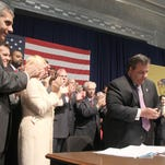 TRENTON - 6/28/2011 - State Senator Joseph Kyrillos (left, R-Monmouth) watches as Governor Chris Christie collects up the pens after signing the pension reform bill at the War Memorial in Trenton Tuesday afternoon. ASBURY PARK PRESS PHOTO BY THOMAS P. COSTELLO - PENSIONBILL0628H - WITH VIDEO