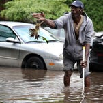 Larry Young, 58, of Highland Park tries to clear out a storm drain in front of his residence on McNichols street in Highland Park, Mich., on Tuesday, Aug. 12.