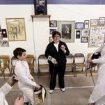 Jacob Prater, 13, of Salem, plugs in his scoring machine at the Salem Fencing Club on Wednesday, March 25, 2015.