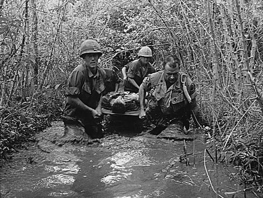 Soldiers carry a wounded comrade through a swampy area