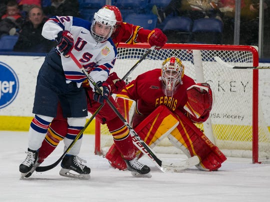 Jake Wise (12) of the U.S. NTDP Under-18 team sets up shop in front of Ferris State netminder Darren Smith.