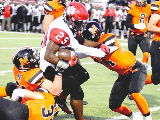 Grand Blanc's Kettrell Ware, Jr. (29) is corraled by the Mustangs' from left) Max Cooper (38), Jordan Grewe and Jake McWilliams (right).
