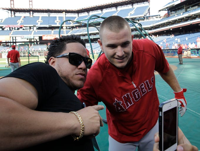 Los Angeles Angels' Mike Trout poses for a photo with Robert Uribe from Reading, Pa, who attended Millville High School in Millville, NJ with Trout, before the start of a baseball game with the Philadelphia Phillies, Tuesday, May 13, 2014, in Philadelphia. (AP Photo/Laurence Kesterson)