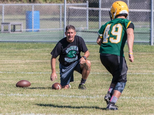 Pennfield head varsity football coach Mike McGuire works with players on the first day of practice on Monday.
