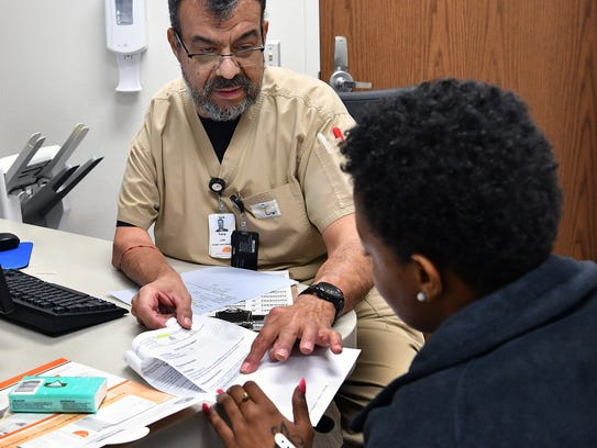 Discharge nurse Tony Ortiz LVN, gives a flu patient