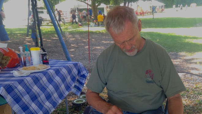Dan Theus of San Antonio, Texas, works a piece of stone into a point at the Stone Tool Craftsman Show on Saturday.