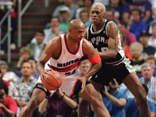 THEN: Suns forward Charles Barkley (left) tries to drive against the San Antonio Spurs' Dennis Rodman in 1994. Barkley wears mid-length shorts with longer tight undershorts displaying the Suns logo.