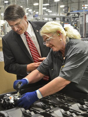 Continental employee Julie Ward shows Governor Pat McCrory a electronic parking brake for a Ford Fusion at the company's expansion event last year. Along with WilsonArt, Continental is hiring. A job fair will be held Saturday.