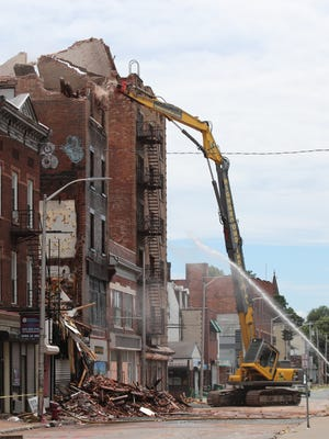Demolition crews work to take down a collapsed building at 17 Academy St. on Wednesday, June 20, 2018.