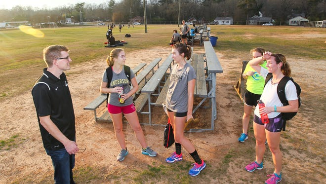Kevin Licht, left, Anderson University's Track and Cross Country coach, meets with Bari Robinson, middle left, Taylor Morris, Rebecca Faircloth, and Emily Pitt after their run near the men's soccer practice at the campus athletic facility in Anderson.