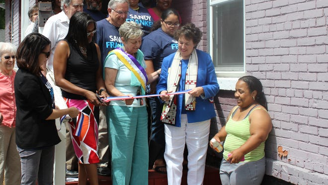 Sandra Frankel, second from right, cuts the ribbon on her new campaign office on North Clinton.