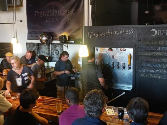 Customers line up inside Darkness Brewing during a