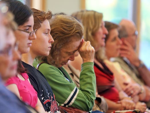 A woman bows her head as several hundred people attended a prayer vigil at Bet Am Shalom Synagogue in White Plains July 1, 2014 for the three Israeli teenagers kidnapped and killed. The five Synagogues of White Plains came together for the vigil, which included prayers, psalms, chanting and reflections on the tragedy.