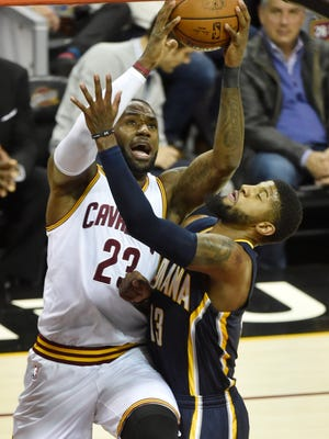 Cleveland Cavaliers forward LeBron James (23) drives against Indiana Pacers forward Paul George (13) in the first quarter at Quicken Loans Arena.