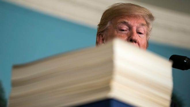 President Trump with the 2,232-page, $1.3 trillion spending bill he signed, March 23, 2018, Washington, D.C.