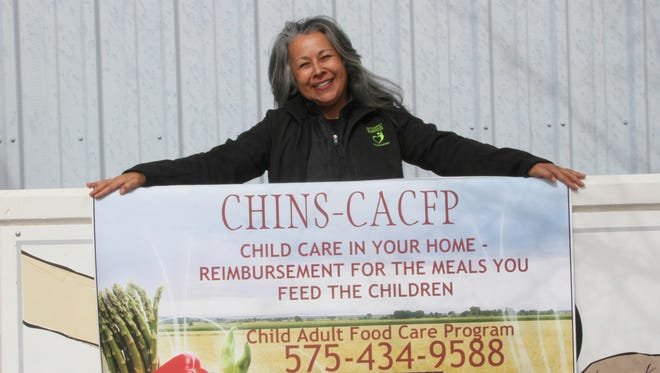 CHINS' Child and Adult Care Food Program coordinator Debra Padilla holds the CHINS-CACFP sign in front of their office building in Alamogordo. The assistance program is offered to both Otero and Lincoln county residents.
