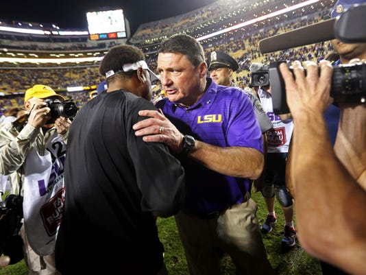 LSU coach Ed Orgeron, right, greets Texas A&M coach Kevin Sumlin after an NCAA college football game in Baton Rouge, La., Saturday, Nov. 25, 2017. LSU won 45-21. (AP Photo/Gerald Herbert)