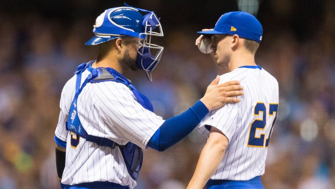 Brewers catcher Manny Pina talks with pitcher Zach Davies (27) during the sixth inning.