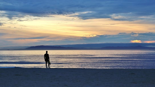 A surfer looks out at the ocean near Ventura Harbor.