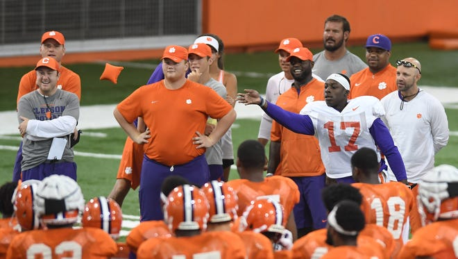 Clemson players take a break to compete in a cornhole competition Monday during practice
