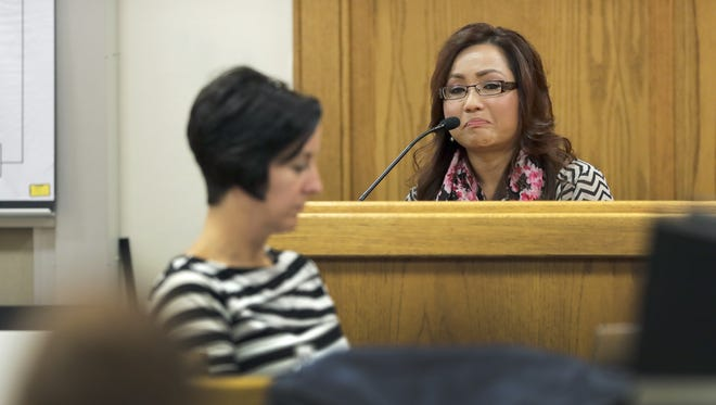 Pachia Lor becomes emotional as she describes the events leading up to her leg being amputated during her testimony against her husband in court Tuesday, Sept. 27, 2016, at the Outagamie County Justice Center in Appleton, Wisconsin. Her husband Zohn Wang Kub Yang is accused of ramming his wife with a vehicle, severing her leg.