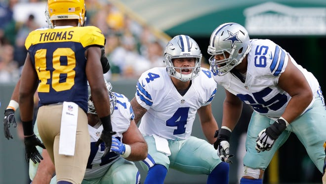 Dallas Cowboys quarterback Dak Prescott runs the offense against the Green Bay Packers defense at Lambeau Field.