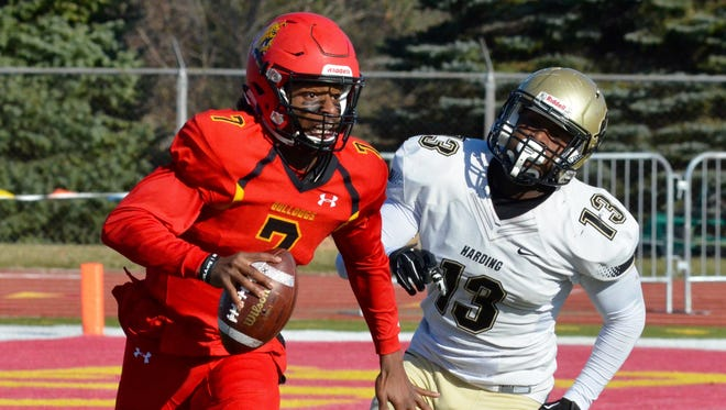 Ferris State quarterback Reggie Bell rushes past Harding defensive end Devyn Comer during the Division II football quarterfinal Saturday, Dec. 2, 2017 at Top Taggart Field in Big Rapids.