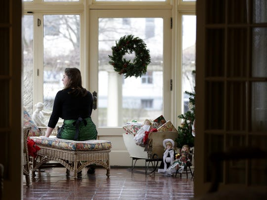 Alaina Goetsch, of Wausau  stares out the window of the Yawkey House Museum while waiting for visitors to enter her display during the Christmas at the Houses event, hosted by the Marathon County Historical Society, in Wausau in 2016.