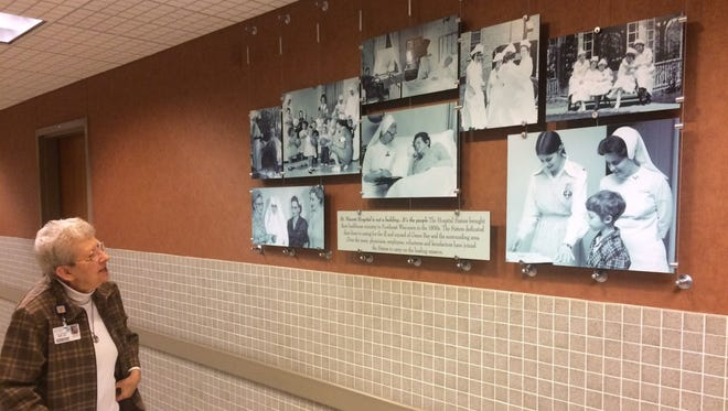 Sister Annice McClure looks at old photographs displayed in a hallway at HSHS St. Vincent Hospital in Green Bay that feature nurses from the Hospital Sisters of St. Francis religious community who worked at the hospital.