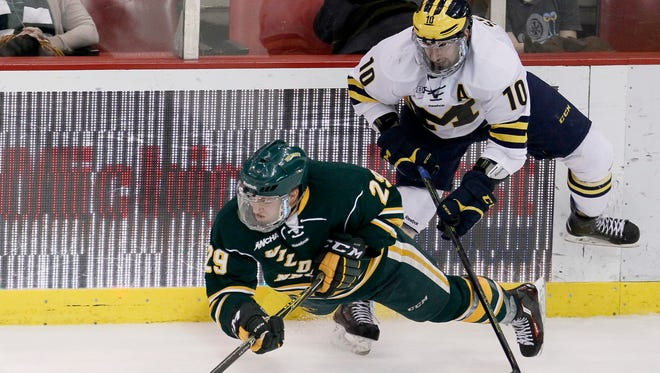 Northern Michigan's Robbie Payne (29) is tripped up by Michigan's Justin Selman (10) during the third period of the Great Lakes Invitational on Dec. 29, 2015, in Detroit.