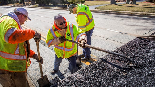 State workers, from left, Rob Wilson, Frank Lowther and John Hanley repair Foulk Road on March 18. Democratic lawmakers on Friday introduced legislation that would raise Division of Motor Vehicles fees to fund road and bridge fixes.
