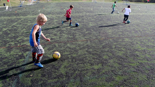 Members of the Avengers team, Sean McCoy, 6, (from left) Nakoa Stilwell, 6, Cane Cervantes, 7, and Josh Cormier, 6, work on their ball handling skills in September 2016 during practice at the Redding Soccer Park. The artificial turf has long been worn down and is the subject of a suit.