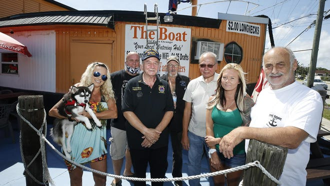 """Drinking establishments like The Boat in Port Orange have been able to get around the state's regulations about keeping bars closed during the pandemic by serving simple food. From left, Port Orange-South Daytona bar owners Jill and Mark Slonicki, Ray """"Rocky"""" Siracusa, Al Bulling, Rich Hurst, Nicole Taylor and Tony Annatone are outside The Boat in July. Annatone had his bar, The Boat, reopened as a restaurant, and now he's fighting for his friends to be able to reopen their establishments as well during the coronavirus pandemic."""