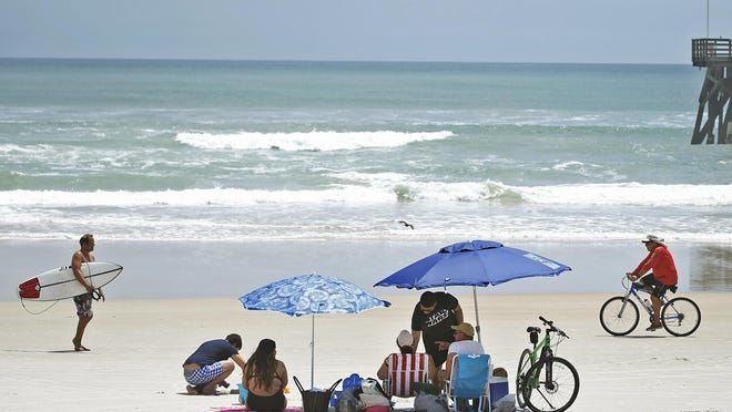A family lounges on the sand earlier this summer in Daytona Beach. With school start dates delayed statewide due to the coronavirus, tourism leaders are shifting advertising resources to attract families that might have more time for an August visit.