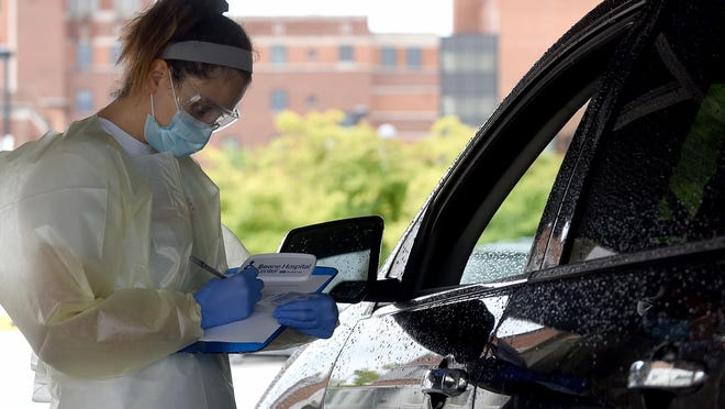 Kennedy Crigler, a laboratory associate at Boone Hospital Center, gets information about a person receiving a COVID-19 test at the hospital's drive-thru testing site off William Street.
