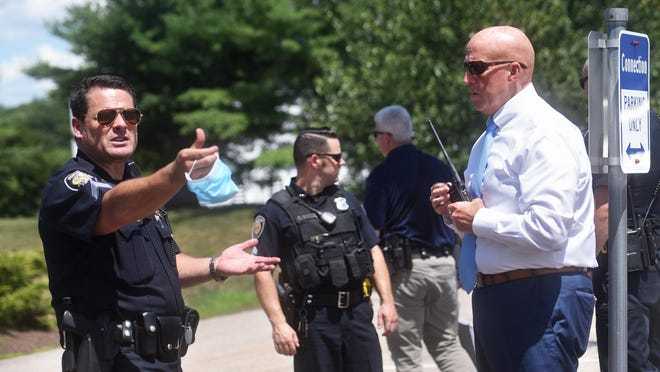 Police Sgt. Kuffer Kaltenborn talks with Portsmouth Police Chief Robert Merner about a suspect's actions before they took him into custody Wednesday afternoon at Pease International Tradeport.