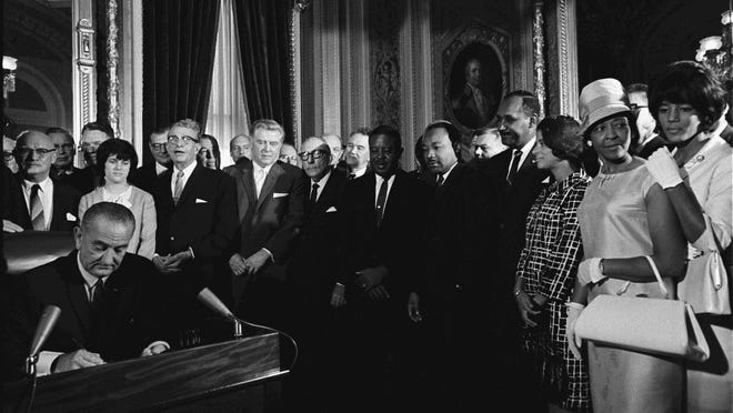 President Lyndon Johnson signs the Voting Rights Act on Aug. 6, 1965, as the Rev. Dr. Martin Luther King Jr. and other civil rights leaders look on. Luci Baines Johnson stands behind the president.