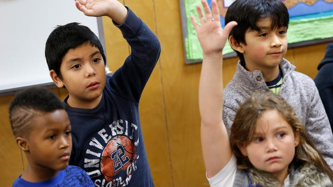 Oscar Banuelos-Bugarin, 7, second from left, raises his hand to answer a question during class at Burnett Creek Elementary in West Lafayette. Teacher Karen Charles turns to Oscar for help when her five English language-learner students can't understand her teaching.