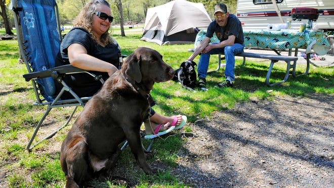 Jennifer Schultz and Teddy Rein relax after setting up camp in Schroeder Park. The couple visits the park a couple of times a year and were waiting for more family members to join for the weekend.