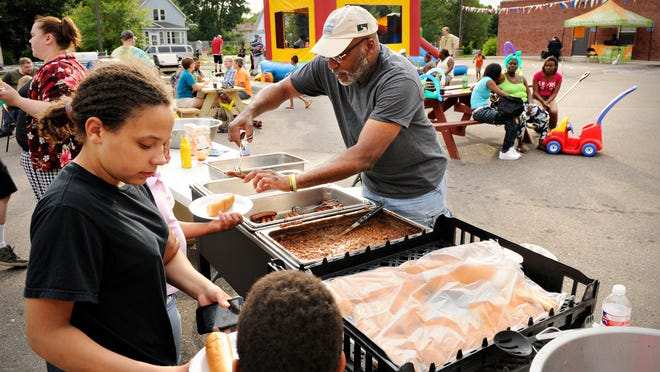 Tyson Baker Sr. was the center of attention as he served food for neighbors gathering for the National Night Out in August 2014 in the parking lot of Place of Hope.