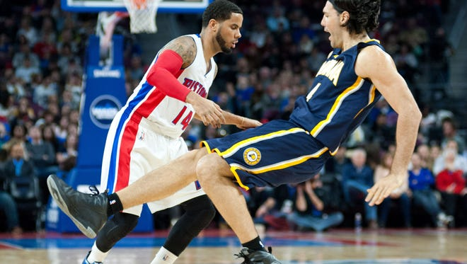 Dec 26, 2014; Auburn Hills, MI, USA; Indiana Pacers forward Luis Scola (4) fouls Detroit Pistons guard D.J. Augustin (14) during the second quarter at The Palace of Auburn Hills. Mandatory Credit: Tim Fuller-USA TODAY Sports