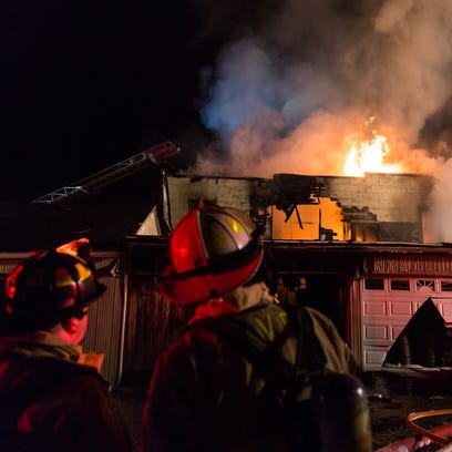Firefighters work at the scene of a third alarm house