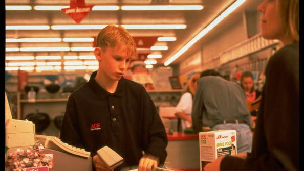 Teenage cashier Brian Fzajna scans gardening supplies for a customer at a check-out counter of a minimum-wage job at Warden's Ace Hardware.