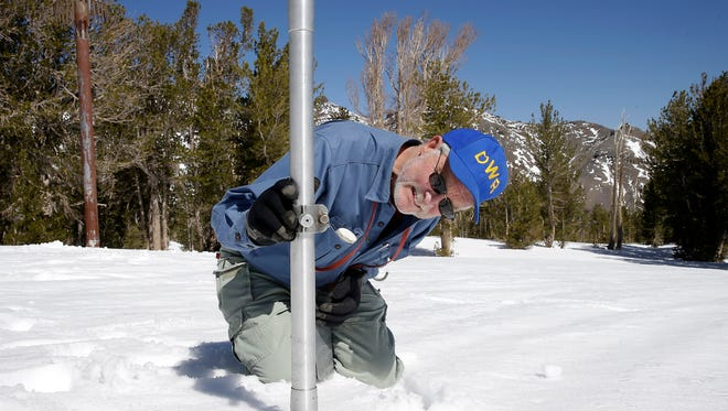 In this April 28, 2015 file photo, Frank Gehrke, chief of the California Cooperative Snow Surveys Program for the Department of Water Resources, checks the depth of the snow pack as he does a snow survey at Leavitt Lake near Bridgeport Calif.