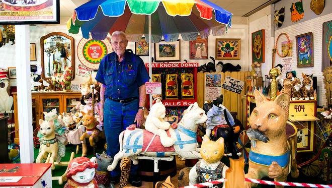 Harold Sims stands amongst the antiques and art pieces in the carnival section of The American Museum of the House Cat outside Sylva that opened in April. Sims, also the owner of the Catman 2 cage-free shelter in Cullowhee, opened the museum to share the countless art, trinkets, and pieces of history with the public that he has collected over the years. Pieces range ancient Egyptian cat sculptures, cat carnival games, cat beer steins from Germany, and even a petrified cat removed from a chimney of a late 16th century English home.
