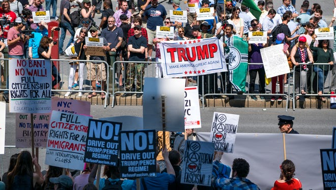 Demonstrators against Islamic law (background) gather in New York Saturday, June 10, 2017, as counter demonstrators line up across Centre St., foreground.
