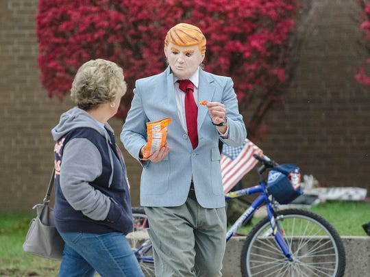 Perennial Livonia political gadfly Leo Weber works the polls at Frost Middle School wearing a Donald Trump mask and passing out candy.