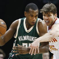 Hawks guard Kyle Korver reaches for the ball as he guards Khris Middleton in the first half Friday, March 25 in Atlanta. The Hawks beat the Bucks, 101-90.